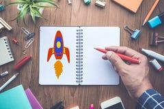 Comece acima conceitos com o foguete do desenho no bloco de notas imagens de stock