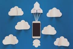 Comece acima ou conceito rápido da conexão O foguete do papel do lançamento com o telefone esperto no céu azul com nuvens origami fotografia de stock