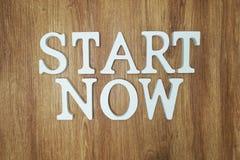 Comece agora letras do alfabeto da palavra no fundo de madeira foto de stock royalty free