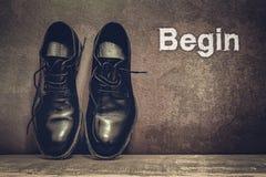Comece em sapatas marrons da placa e de trabalho no assoalho de madeira foto de stock