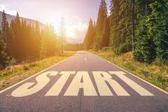 Comece escrito na estrada da montanha, conceito do começo em linha reta para bu Foto de Stock