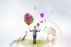 Comedian man with color balloons . Mixed media Stock Image
