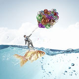 Comedian man with color balloons . Mixed media Royalty Free Stock Photography