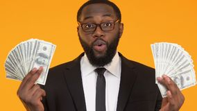 Comedoiro preto feliz no terno que guarda grupos dos dólares, riqueza do investimento de capital filme