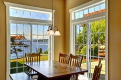 Comedor brillante con la tabla rústica y las ventanas francesas Foto de archivo libre de regalías