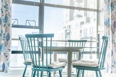 Comedor muy brillante en un apartamento, con las ventanas grandes en el fondo, y sillas azules con una tabla de cristal en imagenes de archivo