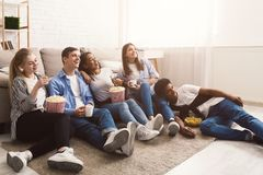 Comedy film. Happy friends watching movie at home. Comedy film. Happy friends watching movie, sitting on floor at home royalty free stock photo
