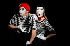 Comedy sketch of mimes. Waist up portrait of men and women on black background, performing a pantomime show. Shock and misunderstanding royalty free stock image