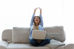 Comemoração bonita da jovem mulher succes ao trabalhar com portátil em casa imagem de stock royalty free