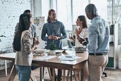 comemoração Grupo diverso de executivos novos que bebem o cha imagens de stock royalty free