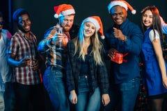 Comemorando o ano novo junto Grupo de jovens bonitos em chapéus de Santa fotografia de stock