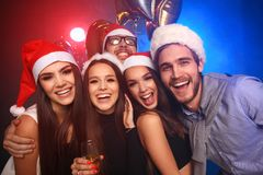 Comemorando o ano novo junto Grupo de jovens bonitos nos chapéus de Santa que jogam confetes coloridos, olhando feliz fotografia de stock royalty free
