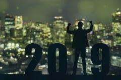 Comemorando a posição nova do homem de negócio da esperança da liberdade da silhueta do ano novo 2019 e apreciação o na parte sup fotografia de stock