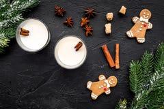 Comemore a noite do inverno do ano novo com bebida da gemada nos vidros cookie do pão do gengibre, ramo spruce e canela preto Foto de Stock