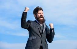 Comemore o sucesso Esperan?oso e seguro sobre o futuro Homem de negócios otimista farpado do homem para vestir o céu formal do te imagem de stock