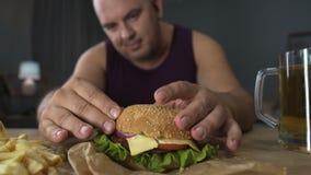 Comendo demais, homem obeso que cozinha o hamburguer grande, gourmet que admira sua refeição, close-up filme