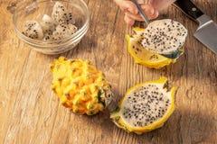 Comendo Dragon Fruit amarelo imagem de stock
