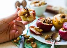 Comendo maçãs cozidas com nozes, mel e canela, sobremesa Fotografia de Stock Royalty Free
