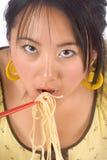 Comendo macarronetes com chopsticks Foto de Stock