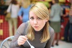 Comendo a menina com a colher no restaurante #1 do fast food imagem de stock