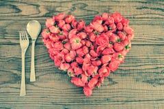Comendo no amor, um coração feito com rosas vermelhas floresce Fotografia de Stock