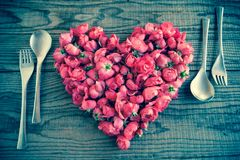 Comendo no amor, um coração feito com rosas vermelhas floresce Imagens de Stock Royalty Free
