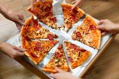 Comendo o alimento Povos que tomam fatias da pizza Lazer dos amigos, F rápido Fotografia de Stock Royalty Free