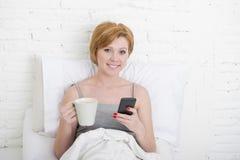 Comendo o café da manhã do coffe na cama ao olhar a notícia do Internet em seu telefone celular em uma comunicação em linha Imagem de Stock Royalty Free