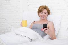 Comendo o café da manhã do coffe na cama ao olhar a notícia do Internet em seu telefone celular em uma comunicação em linha Fotos de Stock Royalty Free