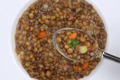 Comendo o guisado da sopa de lentilha com as lentilhas na colher de cima de Fotografia de Stock Royalty Free
