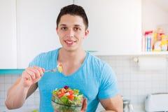 Comendo o homem novo da salada na cozinha saudável coma o copyspac do vegetariano foto de stock royalty free