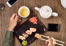 Comendo o sushi com varas de bambu Foto de Stock
