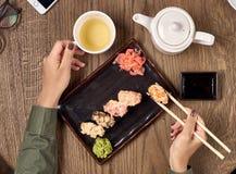 Comendo o sushi com varas de bambu Fotos de Stock Royalty Free