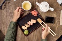 Comendo o sushi com varas de bambu Foto de Stock Royalty Free