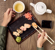 Comendo o sushi com varas de bambu Fotos de Stock