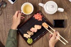 Comendo o sushi com varas de bambu Imagem de Stock