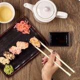 Comendo o sushi com varas de bambu Fotografia de Stock