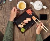 Comendo o sushi com varas de bambu Imagens de Stock