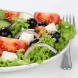 Comendo a salada grega na bacia com tomates, queijo de feta, azeitonas Fotografia de Stock