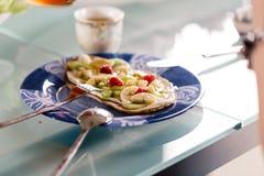 Comendo a sobremesa das panquecas com framboesa, quivi, banana e creme Fotos de Stock