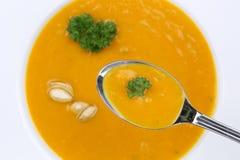 Comendo a sopa da abóbora com as abóboras na colher de cima de Foto de Stock