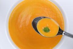 Comendo a sopa da cenoura com as cenouras na colher de cima de Imagens de Stock Royalty Free