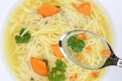 Comendo a sopa de macarronete na bacia com macarronetes e colher Fotos de Stock Royalty Free