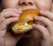 Comendo um hamburguer Imagem de Stock