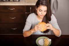 Comendo um hamburguer e fritadas Imagem de Stock Royalty Free