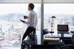Comentario de la prensa de las noticias de la lectura del hombre de negocios en Tablet PC fotos de archivo libres de regalías