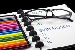 2017 comentarios y 2018 metas mandan un SMS en el sketchbook blanco con la pluma del color y observan los vidrios Fotos de archivo