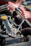 Comenzar al mecánico de coche del enchufe de ignición en la reparación auto Imágenes de archivo libres de regalías