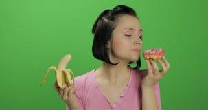Comenzar la consumici?n sana Diga no a la comida basura Bu?uelo o pl?tano bien escogido a comer foto de archivo