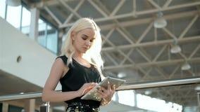 Comenzar nuevo asunto Mujer joven hermosa que sostiene la tableta digital y que mira la cámara con sonrisa mientras que se coloca metrajes